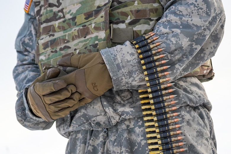 A paratrooper assigned to the 2nd Battalion, 377th Parachute Field Artillery Regiment, 4th Infantry Brigade Combat Team (Airborne), 25th Infantry Division, U.S. Army Alaska, holds a linked belt of 7.62mm ammunition before conducting live-fire qualification at Grezelka range, on Joint Base Elmendorf-Richardson, Alaska, Dec. 5, 2019. The Soldiers practiced identifying, and engaging targets at varying distances to solidify their proficiency with the weapons in sub-arctic conditions.
