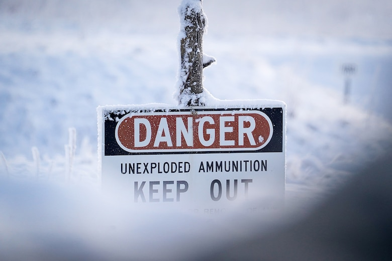 A sign warning of unexploded ammunition is seen covered in hoar frost as paratroopers assigned to the 2nd Battalion, 377th Parachute Field Artillery Regiment, 4th Infantry Brigade Combat Team (Airborne), 25th Infantry Division, U.S. Army Alaska, use M240B, and M2 machine guns while conducting live-fire qualification at Grezelka range, on Joint Base Elmendorf-Richardson, Alaska, Dec. 5, 2019. The Soldiers practiced identifying, and engaging targets at varying distances to solidify their proficiency with the weapons in sub-arctic conditions.