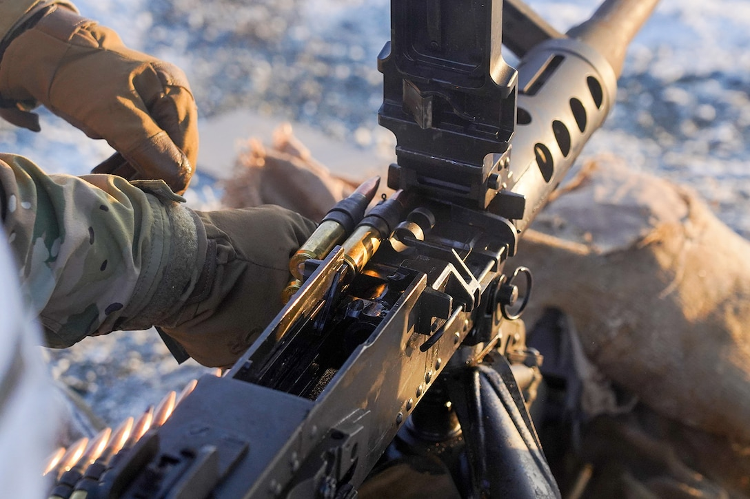 A paratrooper assigned to the 2nd Battalion, 377th Parachute Field Artillery Regiment, 4th Infantry Brigade Combat Team (Airborne), 25th Infantry Division, U.S. Army Alaska, loads an M2 machine gun while conducting live-fire qualification at Grezelka range, on Joint Base Elmendorf-Richardson, Alaska, Dec. 5, 2019. The Soldiers practiced identifying, and engaging targets at varying distances to solidify their proficiency with the weapons in sub-arctic conditions.