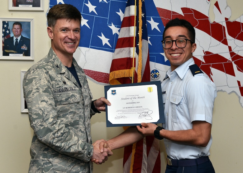 U.S. Air Force Col. Thomas Coakley, 17th Training Group commander, presents the 315th Training Squadron Officer Student of the Month award to 2nd Lt. Roberto Amaya, 315th TRS student, at Brandenburg Hall on Goodfellow Air Force Base, Texas, Dec. 6, 2019. The 315th TRS's vision is to develop combat-ready intelligence, surveillance and reconnaissance professionals and promote an innovative squadron culture and identity unmatched across the U.S. Air Force. (U.S. Air Force photo by Airman 1st Class Robyn Hunsinger/Released)