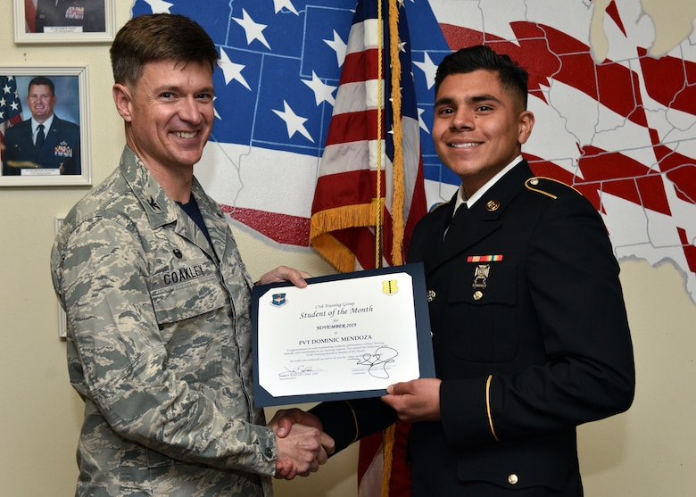 U.S. Air Force Col. Thomas Coakley, 17th Training Group commander, presents the 312th Training Squadron Student of the Month award to Pvt. Dominic Mendoza, 312th TRS student, at Brandenburg Hall on Goodfellow Air Force Base, Texas, Dec. 6, 2019. The 312th TRS's mission is to provide Department of Defense and international customers with mission-ready fire protection and special instruments graduates and provide mission support for the Air Force Technical Applications Center. (U.S. Air Force photo by Airman 1st Class Robyn Hunsinger)