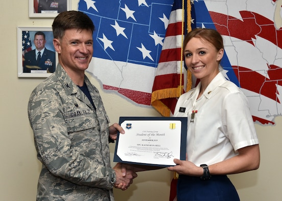 U.S. Air Force Col. Thomas Coakley, 17th Training Group commander, presents the 316th Training Squadron Student of the Month award to Spc. Kathryn Bell, 316th TRS student, at Brandenburg Hall on Goodfellow Air Force Base, Texas, Dec. 6, 2019. The 316th TRS's mission is to conduct U.S. Air Force, U.S. Army, U.S. Marine Corps, U.S. Navy and U.S. Coast Guard cryptologic, human intelligence and military training. (U.S. Air Force photo by Airman 1st Class Robyn Hunsinger)