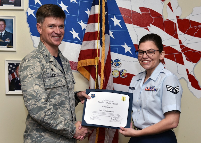 U.S. Air Force Col. Thomas Coakley, 17th Training Group commander, presents the 315th Training Squadron Student of the Month award to Senior Airman Sera Perkins, 315th TRS student, at Brandenburg Hall on Goodfellow Air Force Base, Texas, Dec. 6, 2019. The 315th TRS's mission is to train, educate, and mentor future intelligence, surveillance, and reconnaissance warriors through innovation. (U.S. Air Force photo by Airman 1st Class Robyn Hunsinger)