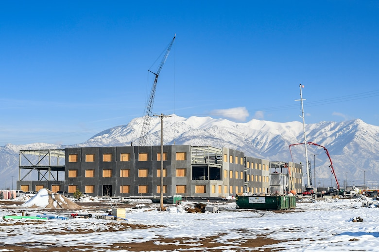 The construction site of the Northrup Grumman Roy Innovation Center situated adjacent to the Hill Aerospace Museum appears with snow covered ground, blue skies, and snow-capped mountains in the background.