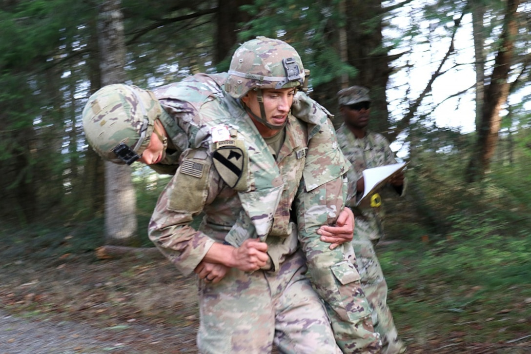 A soldier carries another soldier on his back.