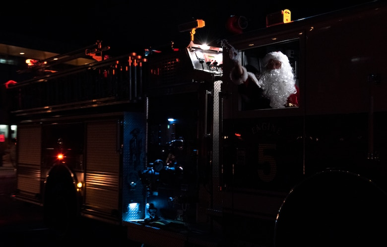 "Santa rides in a fire engine to a tree lighting ceremony Dec. 5, 2019, at Schriever Air Force Base, Colorado. Santa arrived as Orbital Harmony sang ""Here Comes Santa Claus,"" and brought candy and gifts for attendees. He stayed after the tree lighting to eat cookies, drink hot chocolate, and pose for photos with participants. (U.S. Air Force photo by Airman Amanda Lovelace)"