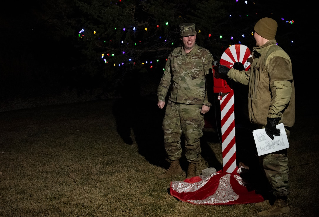 Airman 1st Class Joshua Martin, 50th Operations Support Squadron student, left, and Airman 1st Class John Carmichael, 50th OSS space systems operator, right, flip a switch during the tree lighting ceremony Dec. 5, 2019, at Schriever Air Force Base, Colorado. Dorm Airmen volunteered and were thanked for helping during their first holiday ceremony on an Air Force installation. (U.S. Air Force photo by Airman Amanda Lovelace)