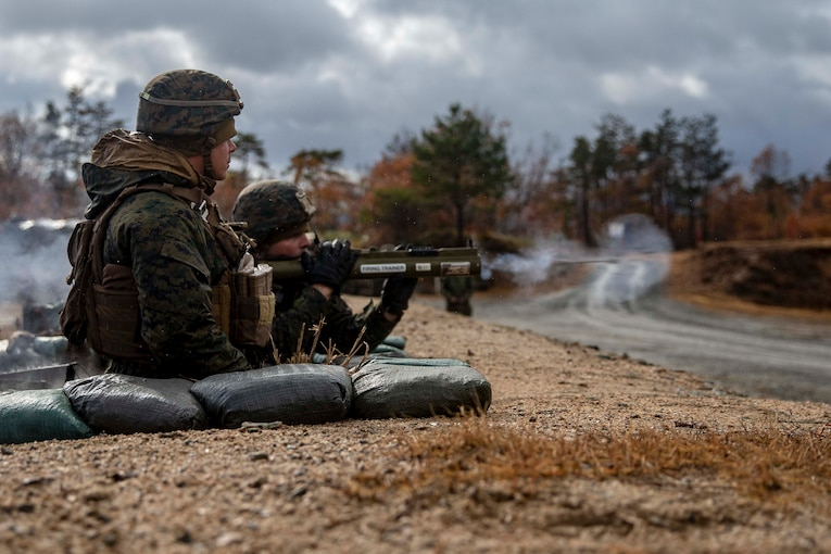 Two Marines fire a weapon.