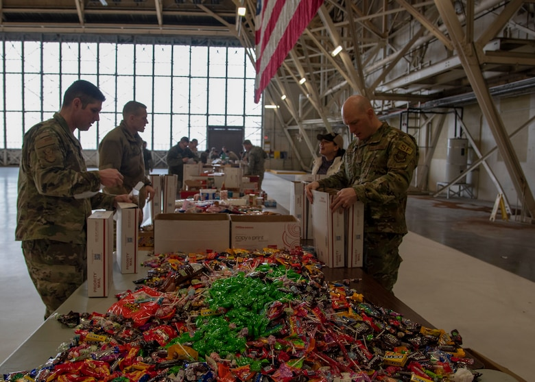 Active duty and civilian volunteers pack holiday care packages for overseas deployed troops at Fairchild Air Force Base, Washington, Dec. 3, 2019.