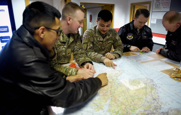 Airmen with the 100th Operations Support Squadron and 351st Air Refueling Squadron discuss potential combat crew communication practices during a briefing at RAF Mildenhall, England, Dec. 3, 2019. The combat crew communications shop's main goal is to ensure the security of all aircrew communications during their flights. This includes training aircrew on the use of a variety of materials to help securely talk over the air. (U.S. Air Force photo by Senior Airman Brandon Esau)