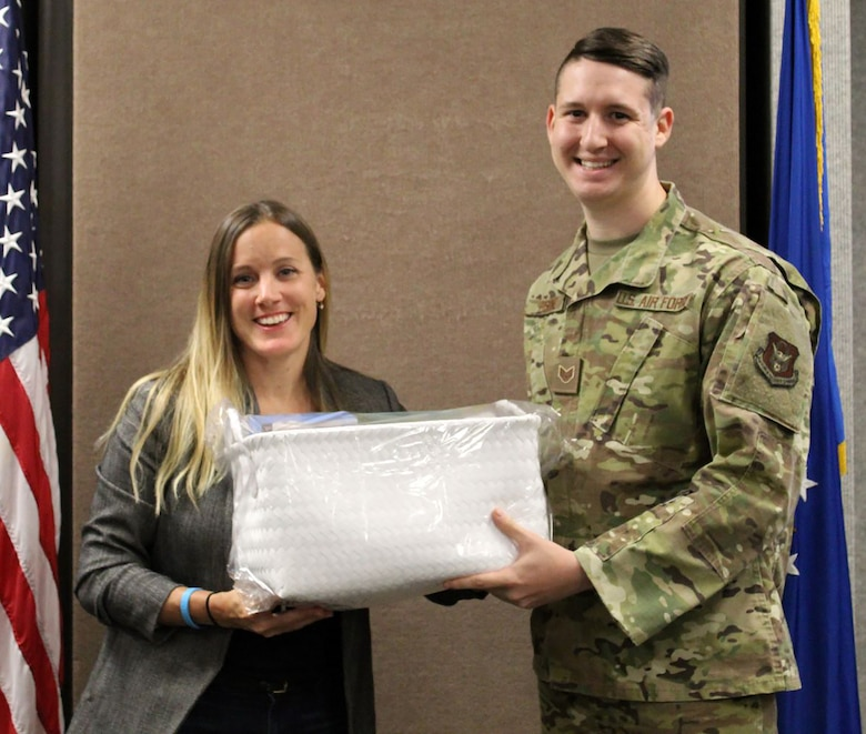 Rebecca Brooks, wife of Lt. Col. Brian Brooks, 718th Intelligence Squadron commander, presents a baby basket to Staff Sgt. Erskine, 718th IS, whose son was born Thanksgiving day. The 718th's Key Spouse program is currently focusing on deployed families and expecting families. Mrs. Rebecca Brooks, and three of the 718th IS members' spouses have been dedicated in the Key Spouse program since September 2018.