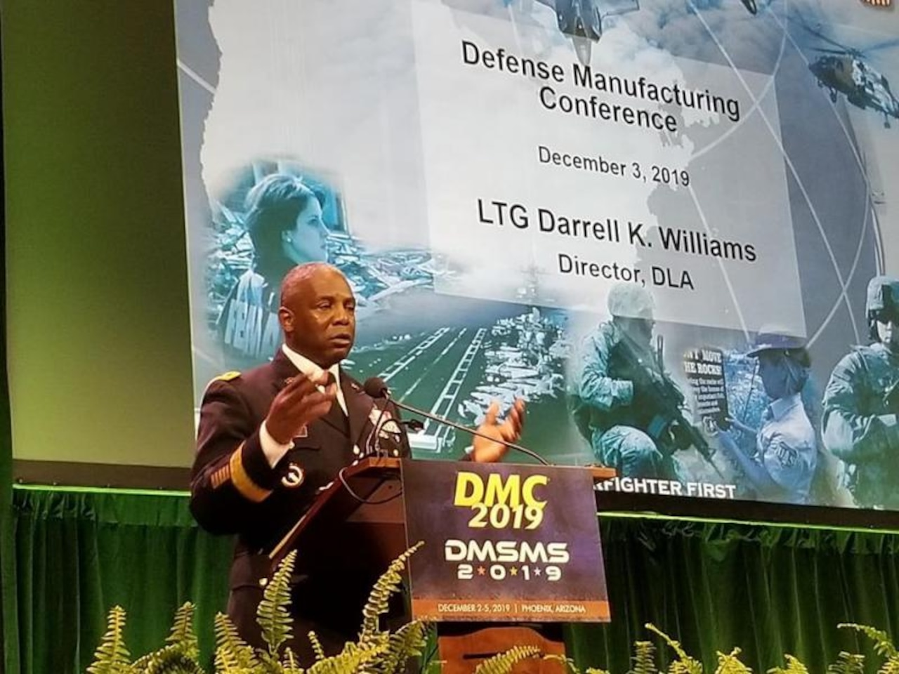 Man speaks at podium during the 2019 Defense Manufacturing Conference Dec. 3
