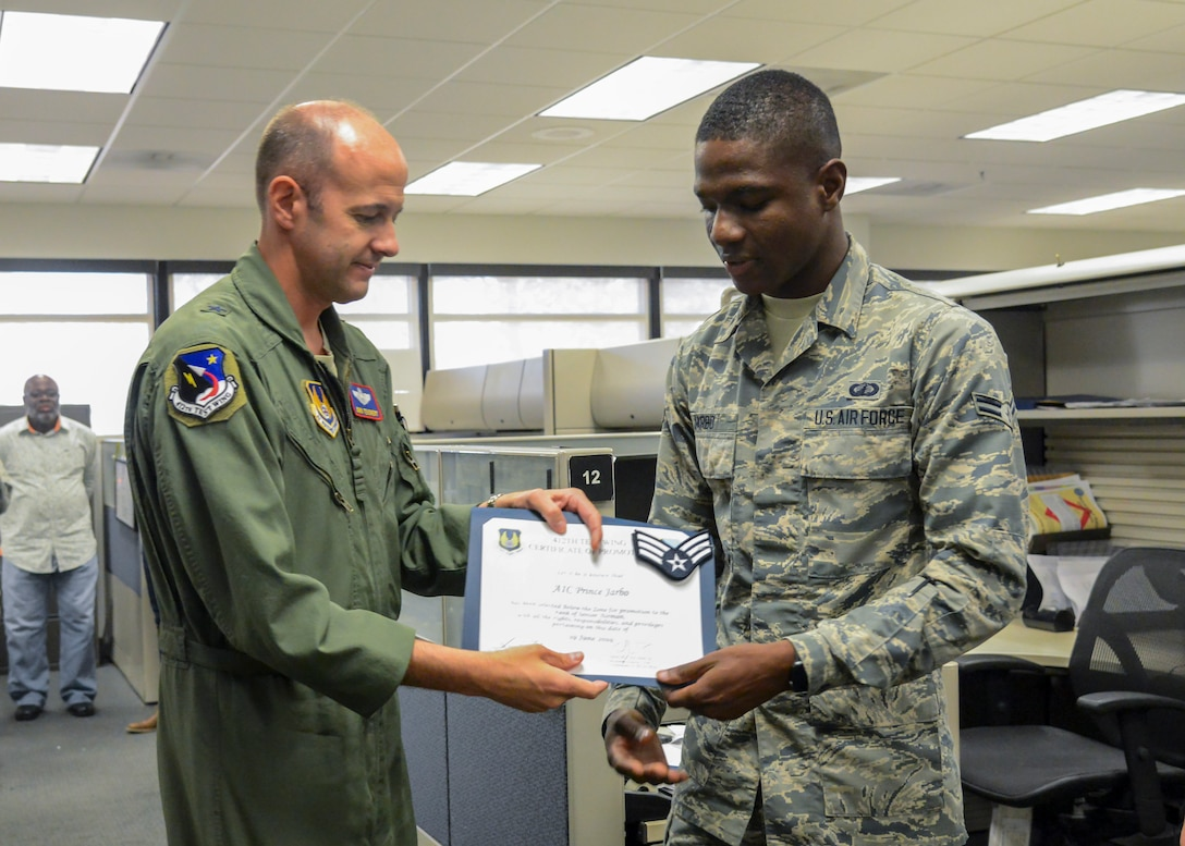 412th Test Wing Commander, Brig. Gen. E. John Teichert, presents a certification of promotion to Senior Airman Prince Jarbo, 412th Comptroller Squadron, June 19. (Air Force photo by Giancarlo Casem)