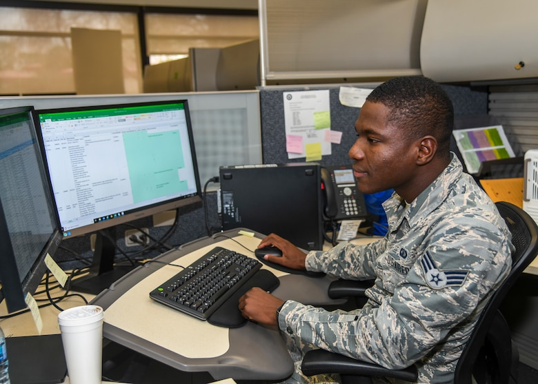 Senior Airman Prince Jarbo, 412th Comptroller Squadron, conducts checks on travel claims at his desk at Edwards Air Force Base, California, Dec. 4. (Air Force photo by Giancarlo Casem)