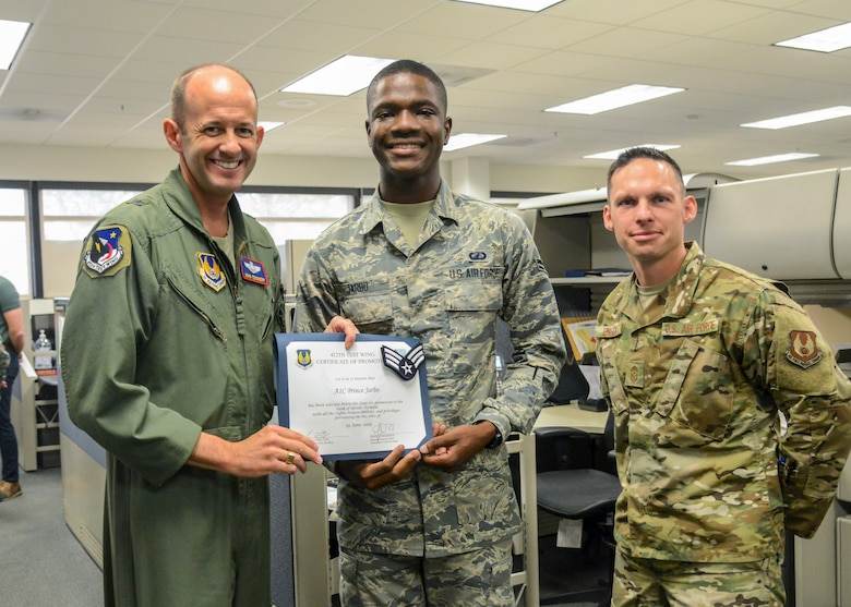 Senior Airman Prince Jarbo, 412th Comptroller Squadron, poses for a photo with Brig. E. John Teichert, 412th Test Wing Commander, and Command Chief Master Sgt. Ian Eishen, 412th Test Wing Command Chief, during his promotion ceremony at Edwards Air Force Base, California, June 19. (Air Force photo by Giancarlo Casem)