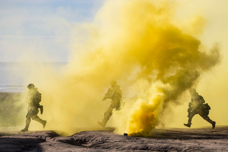 Three Marines run through a cloud of yellow smoke on a beach.