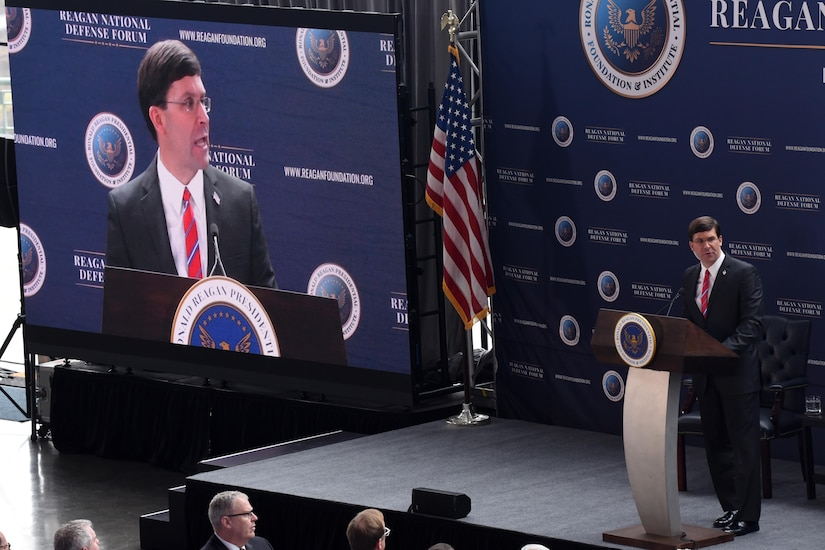 Defense Secretary Dr. Mark T. Esper speaks at a podium while also being shown on a large screen to his right.