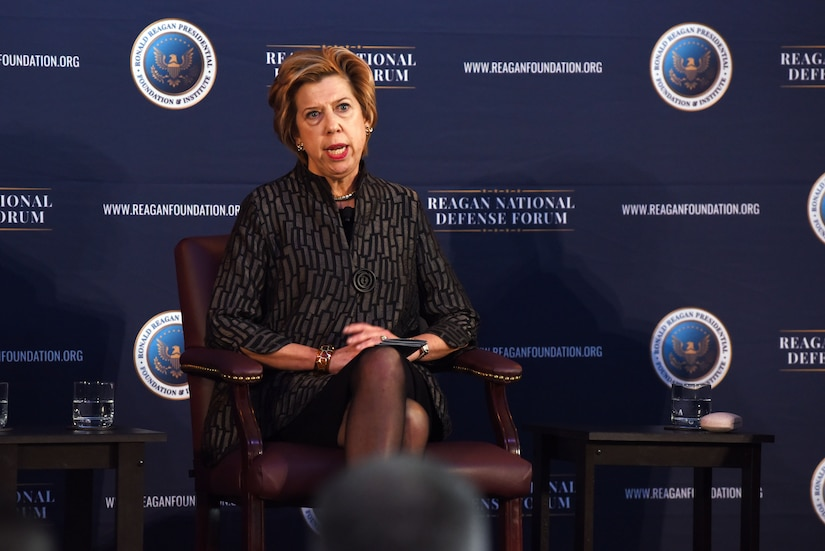 """A woman sits in a leather chair. Behind her, a backdrop reads """"Reagan National Defense."""""""