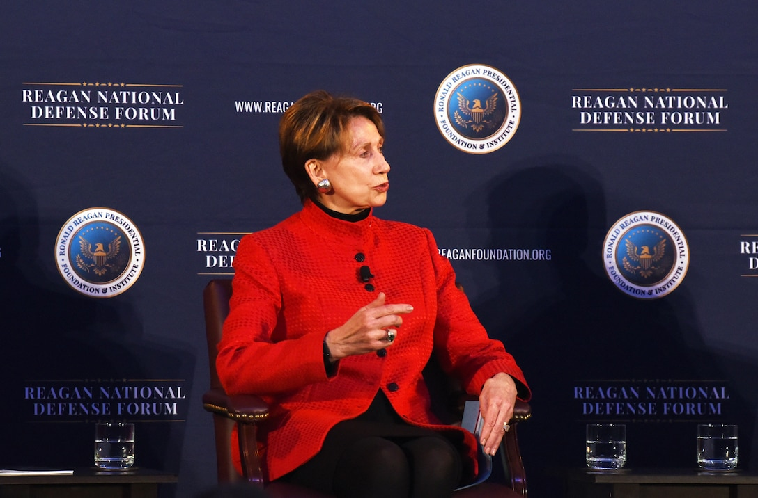 "A woman sits in a chair on stage. A backdrop reads ""Reagan National Defense Forum."""