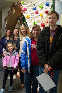 Members of Grissom's Key Spouse program, and their children, pose for a picture under the gingerbread house constructed at the base finance office at Grissom Air Reserve Base, Ind., Dec. 8, 2019. Military and civilian personnel throughout the base decorated their office doors as part of a holiday-themed contest. (U.S. Air Force photo/Staff Sgt. Courtney Dotson-Essett)