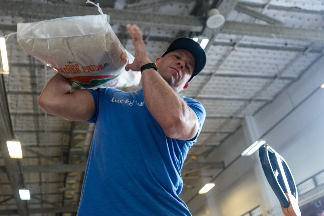 A volunteer lifts a bag of rice