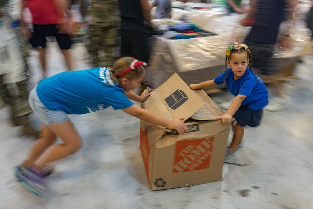 Volunteers slide a box of clothes