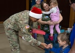 Alaska Army National Guard Sgt. Randall Andrew, an infantryman assigned to the National Guard Readiness Center in Bethel, Alaska, gives a child a gift during Operation Santa Claus in Napakiak, Alaska, Dec. 3, 2019.