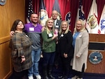 Tyler Phillips stands with his family after taking the oath of enlistment from his grandfather Daniel Phillips, a former Troop Commander in the 1-150th Cavalry Regiment, West Virginia Army National Guard. Tyler enlisted as a 19D cavalry scout in the West Virginia Army National Guard's 1st Squadron, 150th Cavalry Regiment, 30th Armored Brigade Combat Team, in Charleston, West Virginia, Nov. 23, 2019. Tyler's father is Command Sgt. Maj. James Phillips, command sergeant major of the 1-150th Cavalry Regiment, 30th Armored Brigade Combat Team and is deployed to the Middle East. He watched the ceremony over a video chat app on his cell phone.