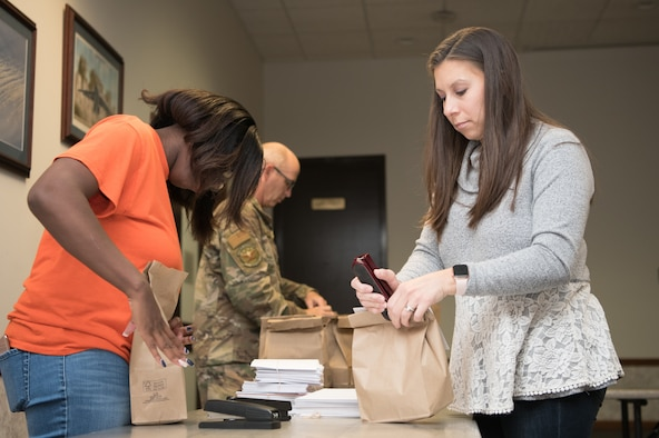 From left to right, Casey Hill and Amanda Habbestad attached greeting cards to bags of cookies during Operation Cookie Drop Dec. 9, 2019, at the 9th Airlift Squadron on Dover Air Force Base, Del. Each bag contains a dozen cookies, along with a greeting card from a member of the local community. (U.S. Air Force photo by Mauricio Campino)