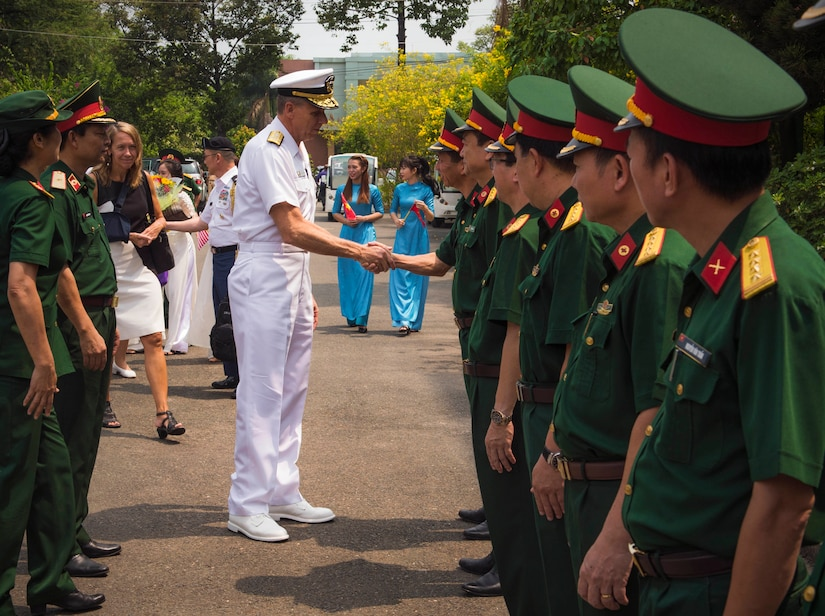 Navy admiral in white uniform shakes hands with one of several Vietnamese military personal lined up wearing green uniforms.