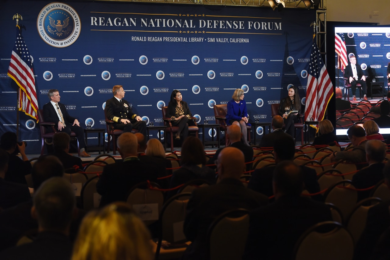 Navy admiral in uniform sits among four civilian panelists in front of an audience.
