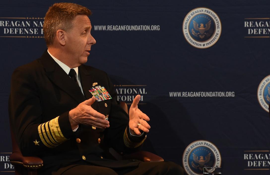 Navy admiral in uniform gestures while speaking.