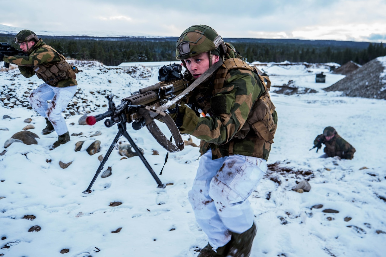 Soldiers with weapons advance in snow.