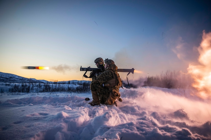 Two Marines kneel on a snowbank as a projectile emerges from a shoulder-launched weapon one of the Marines is firing.