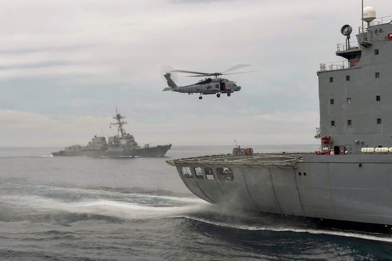 A helicopter flies over a ship as another ship travels in the background.