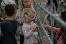 a photo of A child holding a bunny during a base holiday event.