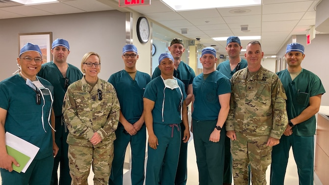 After the huddle, the Army, Navy and Air Force surgeons and Physician Assistant met with the hospital command team. (Left to Right) Col. Alfonso Alarcon, Orthopedic Surgeon at BDAACH, Maj, Harry Aubin, General Surgeon at BDAACH, Command Sgt. Maj. Nicole Haines, the hospital senior enlisted advisor, Capt. Christopher Ng, Air Force General Surgeon with 51st MDG, Maj. Eric de la Cruz, Chief of General Surgery at BDAACH, LCDR Paul Lewis and LCDR Dan Sanford, General Surgeons with 3rd Medical Battalion, Navy, Maj. John Fletcher, General Surgeon at BDAACH, Col. Andrew L. Landers, Hospital Commander, and Capt. Steven Maya, Air Force Physician Assistant with 51st MDG. (Courtesy photo by Inkyeong Yun)