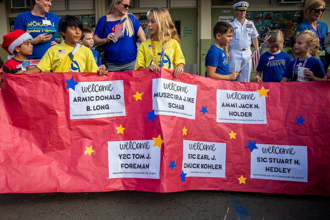 Students with Mokapu Elementary School hold a sign during a U.S. Navy veterans visit to Marine Corps Base Hawaii, Dec. 5, 2019. The Best Defense Foundation returned 6 WWII Pearl Harbor and Naval Air Station Kaneohe Bay survivors to Hawaii for the 78th Commemoration of Pearl Harbor and Naval Air Station Kaneohe Bay which is now MCBH. The heroes returned were Jack Holder US NAVY - Naval Air Station, Kaneohe Bay; Tom Foreman US Navy - USS Cushing; Ira Schab US Navy - USS Dobbin; Stuart Hedley US Navy - USS West Virginia; Donald Long US Navy - Naval Air Station, Kaneohe Bay; and Chuck Kohler US Navy - USS Hornet.