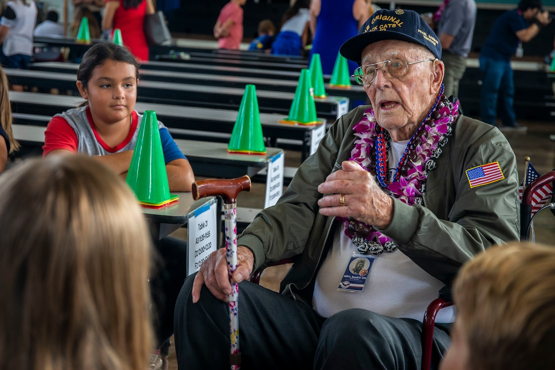Donald Long, retired U.S. Navy radio operator, speaks to students with Mokapu Elementary School during his visit to Marine Corps Base Hawaii, Dec. 5, 2019. The Best Defense Foundation returned 6 WWII Pearl Harbor and Naval Air Station Kaneohe Bay survivors to Hawaii for the 78th Commemoration of Pearl Harbor and Naval Air Station Kaneohe Bay which is now MCBH. The heroes returned were Jack Holder US NAVY - Naval Air Station, Kaneohe Bay; Tom Foreman US Navy - USS Cushing; Ira Schab US Navy - USS Dobbin; Stuart Hedley US Navy - USS West Virginia; Donald Long US Navy - Naval Air Station, Kaneohe Bay; and Chuck Kohler US Navy - USS Hornet.