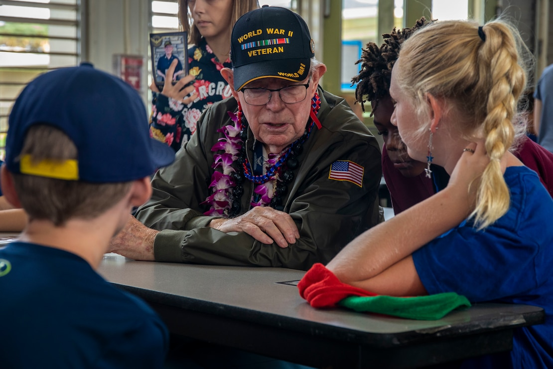 Tom Foreman, retired U.S. Navy gun director, speaks to students with Mokapu Elementary School during his visit, Marine Corps Base Hawaii, Dec. 5, 2019. The Best Defense Foundation returned 6 WWII Pearl Harbor and Naval Air Station Kaneohe Bay survivors to Hawaii for the 78th Commemoration of Pearl Harbor and Naval Air Station Kaneohe Bay which is now MCBH. The heroes returned were Jack Holder US NAVY - Naval Air Station, Kaneohe Bay; Tom Foreman US Navy - USS Cushing; Ira Schab US Navy - USS Dobbin; Stuart Hedley US Navy - USS West Virginia; Donald Long US Navy - Naval Air Station, Kaneohe Bay; and Chuck Kohler US Navy - USS Hornet.