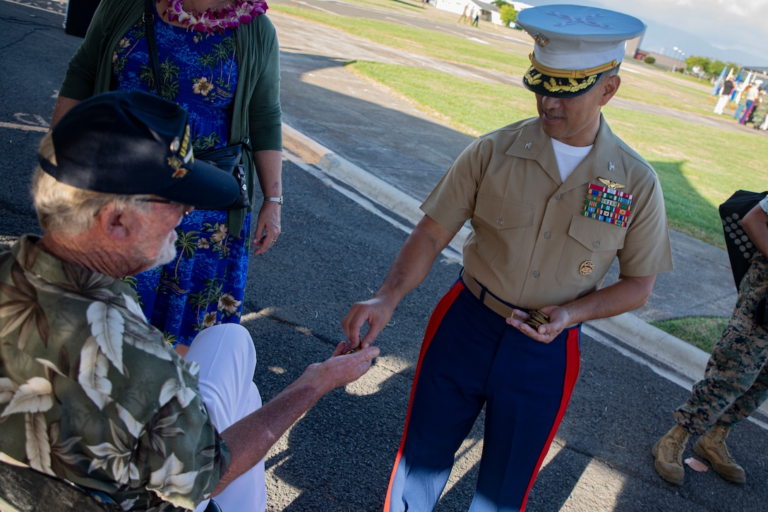 U.S. Marine Corps Col. Raul Lianez, commanding officer, Marine Corps Base Hawaii, gives Mr. Daniel Griffin, a veteran whose father was present during the attack on Naval Air Station Kaneohe Bay, casings from the 21-gun salute after the annual Klipper Ceremony, Marine Corps Base Hawaii, Dec. 7, 2019. The Klipper Memorial was dedicated in 1981 to honor the 17 U.S. Navy Sailors and two civilian contractors who died during the attack on Naval Air Station Kaneohe Bay on Dec. 7, 1941.