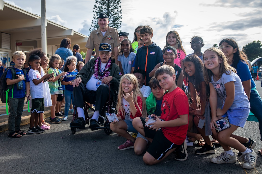 Donald Long, retired U.S. Navy radio operator, and students with Mokapu Elementary School pose for a group photo during Long's visit to Marine Corps Base Hawaii, Dec. 5, 2019. The Best Defense Foundation returned 6 WWII Pearl Harbor and Naval Air Station Kaneohe Bay survivors to Hawaii for the 78th Commemoration of Pearl Harbor and Naval Air Station Kaneohe Bay which is now MCBH. The heroes returned were Jack Holder US NAVY - Naval Air Station, Kaneohe Bay; Tom Foreman US Navy - USS Cushing; Ira Schab US Navy - USS Dobbin; Stuart Hedley US Navy - USS West Virginia; Donald Long US Navy - Naval Air Station, Kaneohe Bay; and Chuck Kohler US Navy - USS Hornet.
