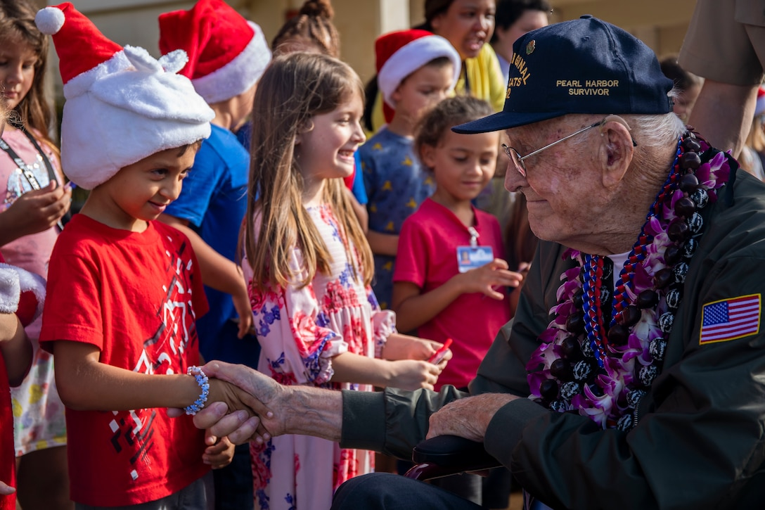 Donald Long, retired U.S. Navy radio operator, shakes a student with Mokapu Elementary School's hand during his visit to Marine Corps Base Hawaii, Dec. 5, 2019. The Best Defense Foundation returned 6 WWII Pearl Harbor and Naval Air Station Kaneohe Bay survivors to Hawaii for the 78th Commemoration of Pearl Harbor and Naval Air Station Kaneohe Bay which is now MCBH. The heroes returned were Jack Holder US NAVY - Naval Air Station, Kaneohe Bay; Tom Foreman US Navy - USS Cushing; Ira Schab US Navy - USS Dobbin; Stuart Hedley US Navy - USS West Virginia; Donald Long US Navy - Naval Air Station, Kaneohe Bay; and Chuck Kohler US Navy - USS Hornet.