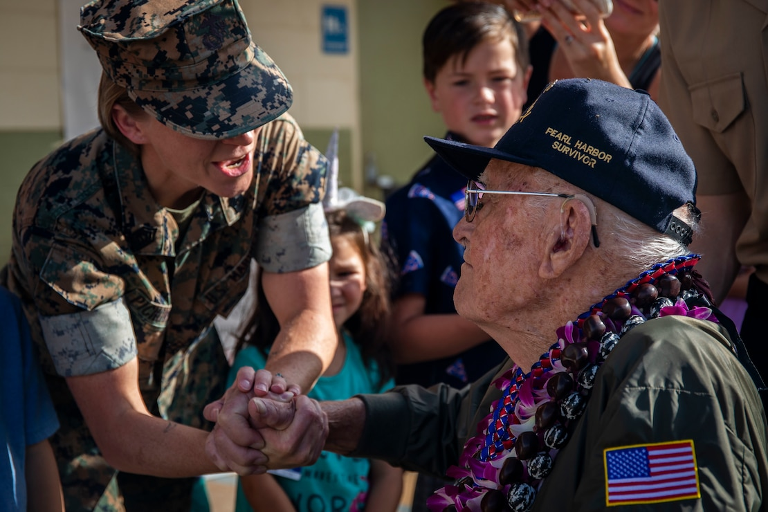 Donald Long, retired U.S. Navy radio operator, shakes a U.S. Marine's hand during his visit to Marine Corps Base Hawaii , Dec. 5.