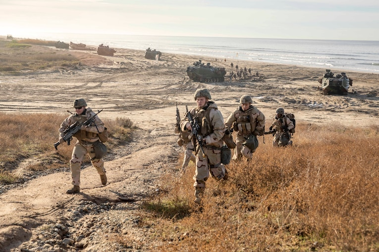 Marines charge on a beach .