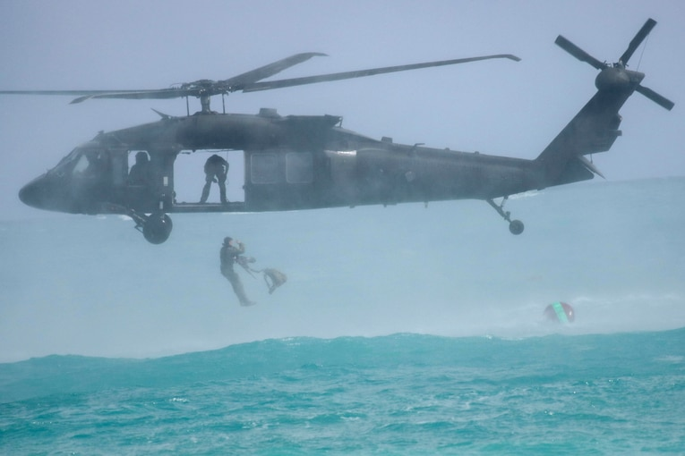 Soldiers jump from a helicopter into water.