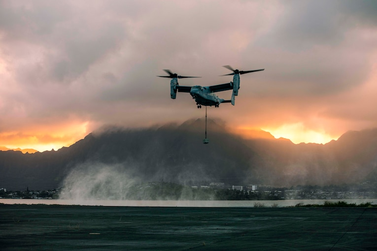 An aircraft carries a cement block hanging on a rope as the sun set.