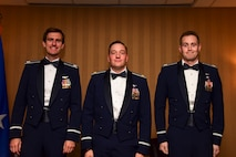 Photo of three Airmen standing on stage
