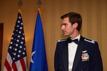 Photo of an Airman next to a U.S. and Air Force flag