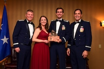 Photo of a U.S. Air Force pilot with his wife, and two other Airmen posing for a group photo with the pilot of the year award